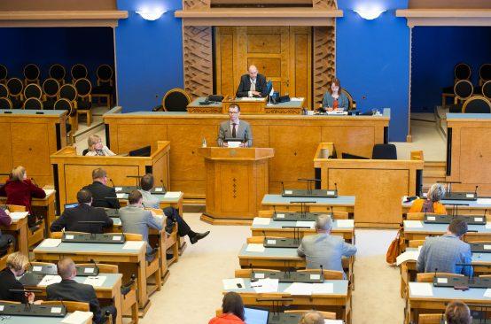 Istungi juhataja oma töölaua taga, taamal valitsusliikmete ja presidendi kohad